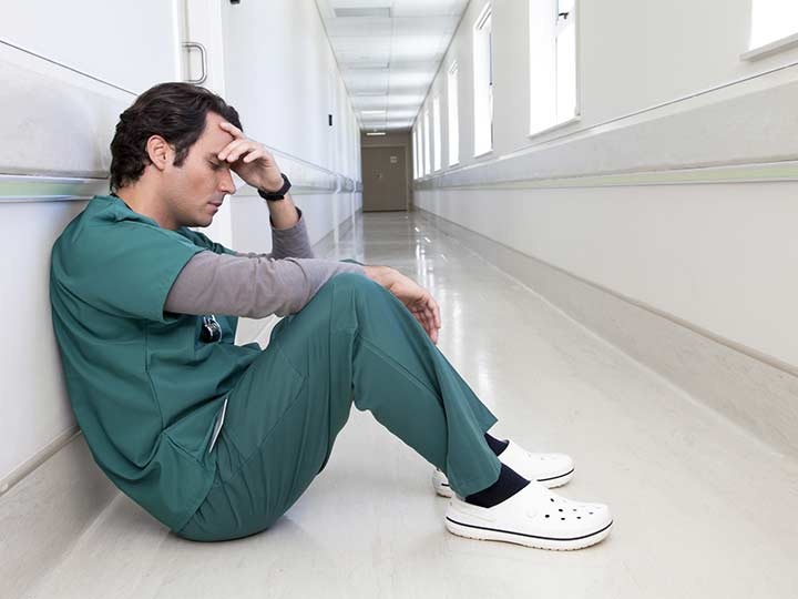 Tired doctor in green scrubs sits on floor in hospital's white corridor